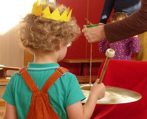 Kleiner Junge mit Papierkrone und Gong in der Hand